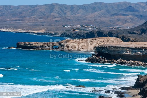Landscape with yellow send, blue sea, big white waves, sea steep cliffs and mountain peaks in nature park of Jandia on deserted island Fuerteventura in spring
