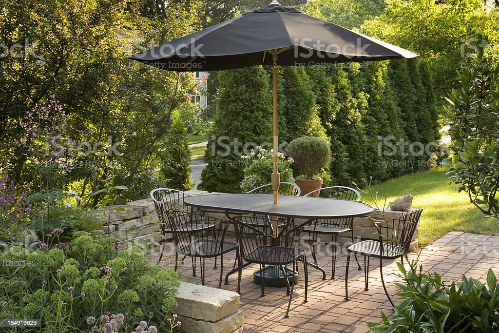 \'Subject: A warm patio with cozy seating and a shade umbrella...