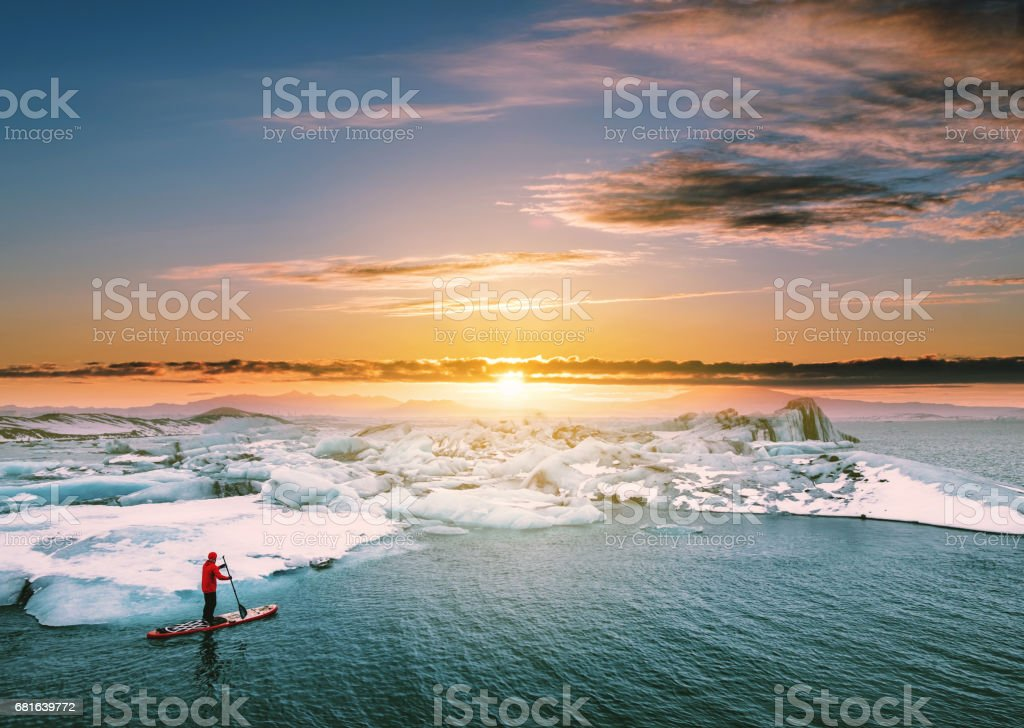 Landscaped, Beautiful glacier lagoon in sunset with a guy paddle boarding ストックフォト