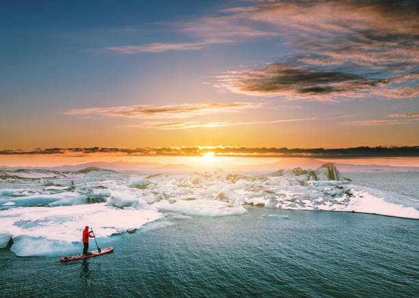 Landscaped, Beautiful glacier lagoon in sunset with a guy paddle boarding stock photo