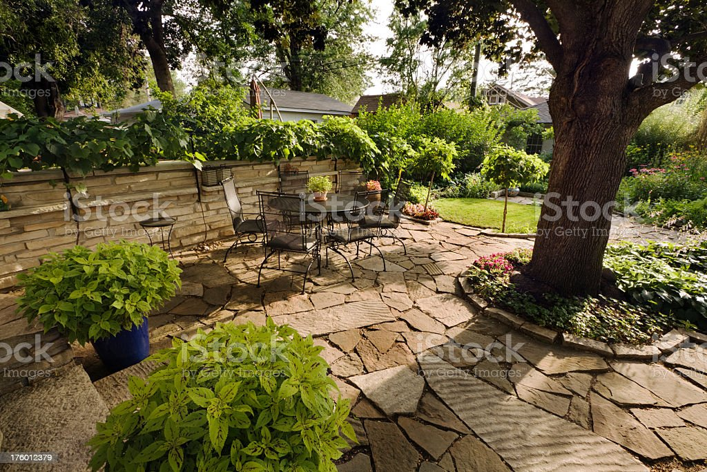 Landscaped Garden Back Yard Patio with Stone Wall, Pavers, Furniture royalty-free stock photo