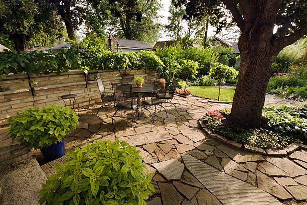gestalteten garten hinterhof terrasse mit steinmauer, es werden pflastersteine verlegt, möbel - naturstein terrasse stock-fotos und bilder