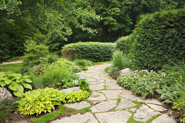 landschaftlich gestalteter patio mit eleganter, ziergärten, blumen und stein weg - naturstein terrasse stock-fotos und bilder