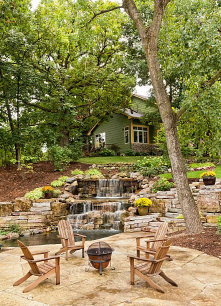 landschaftlich gestalteter patio mit wasserfall - naturstein terrasse stock-fotos und bilder