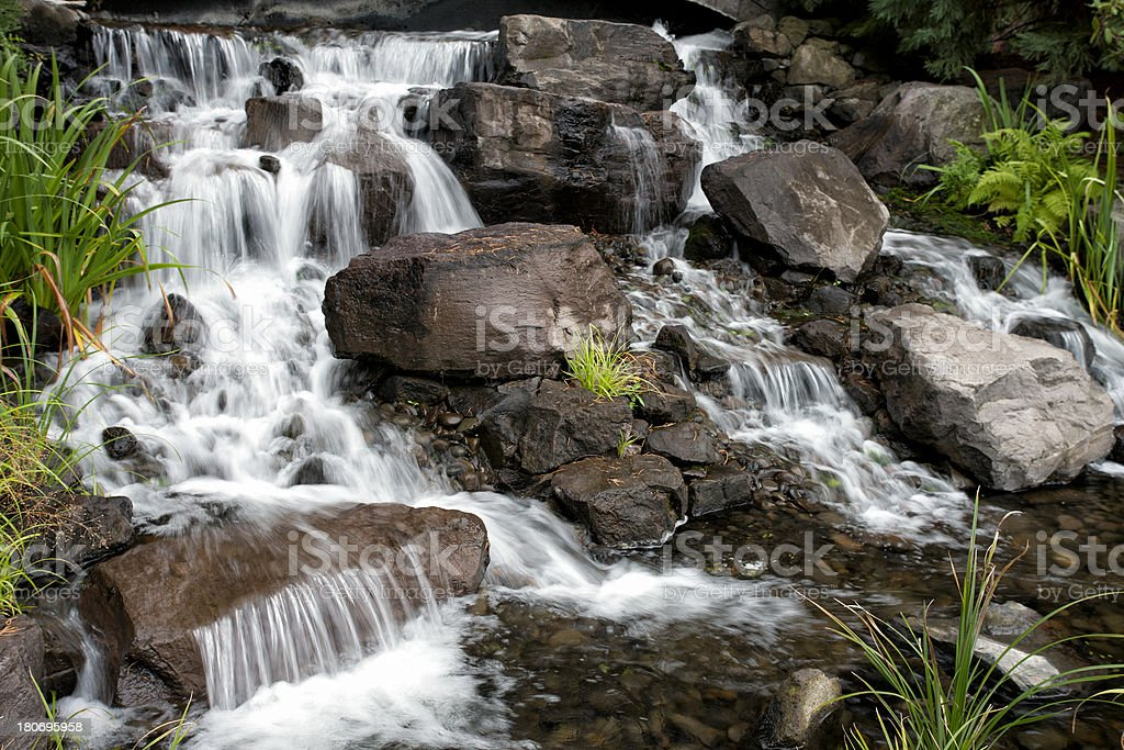 Landscaped waterfall sourrounded by green foliage royalty-free stock photo