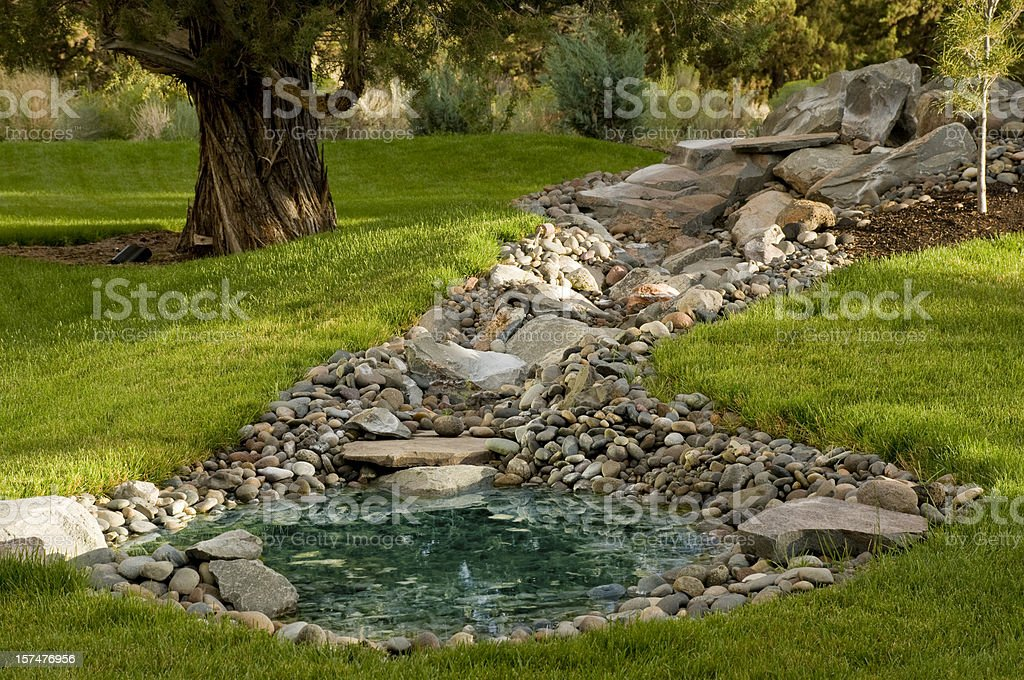 Landscaped yard with pond on grass hill stock photo