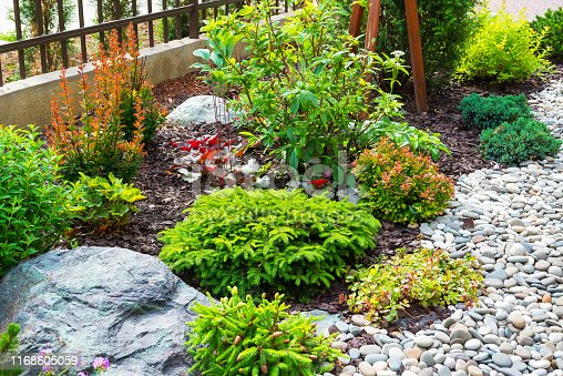 Landscaping in home garden. Beautiful natural landscape design with flower beds in summer. Scenic view of landscaped part with plants and stones in yard or backyard of residential house.