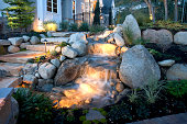 A beautiful landscaped back yard at dusk with landscape lighting.