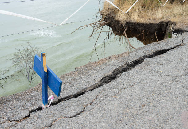 Landslide, cracks in the asphalt road near the sea. Danger of collapse. Landslide, cracks in the asphalt road near the sea. Danger of collapse. devolve stock pictures, royalty-free photos & images