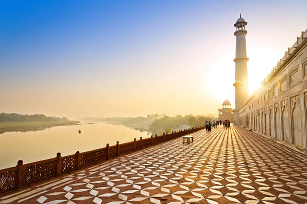 lane around the Tah Mahal at sunrise Tourists walking around the Tah Mahal at sunrise agra stock pictures, royalty-free photos & images