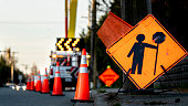 istock Lane closure on a busy road due to maintenance signs detour traffic temporary street work orange lighted arrow, barrels, and cones. 1246882564