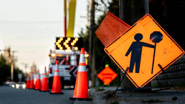 lane stängning på en trafikerad väg på grund av underhållsskyltar omväg trafik tillfälligt gatuarbete orange upplyst pil, fat och kottar. - temporär bildbanksfoton och bilder