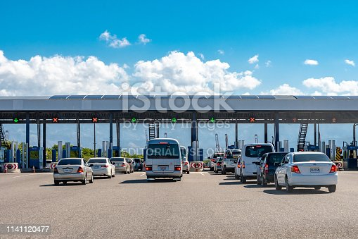 Portmore, Jamaica - March 19 2019: Lanes of cars in traffic at the Portmore Toll Plaza on the Causeway/Highway to Kingston