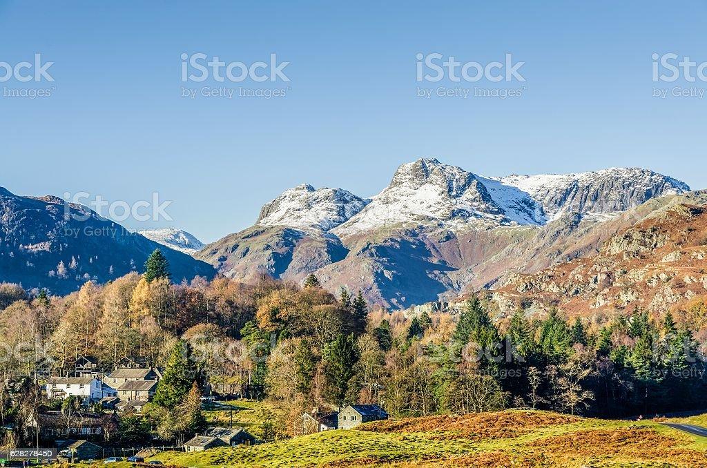 Langdale Pikes over Elterwater village, English Lake District, UK stock photo