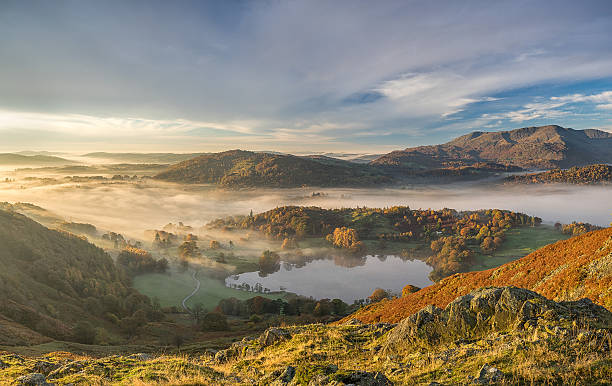 Langdale Valley Autumn Sunrise A view from the top of Loughrigg Fell in the Lake District UK, looking across the Langdale valley shrouded in fog, as the rising sun casts a golden light across the scene english lake district stock pictures, royalty-free photos & images