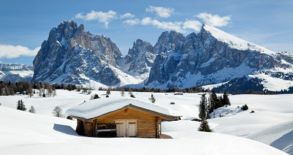 Langkofel mountains and wooden stable in snow covered Dolomites