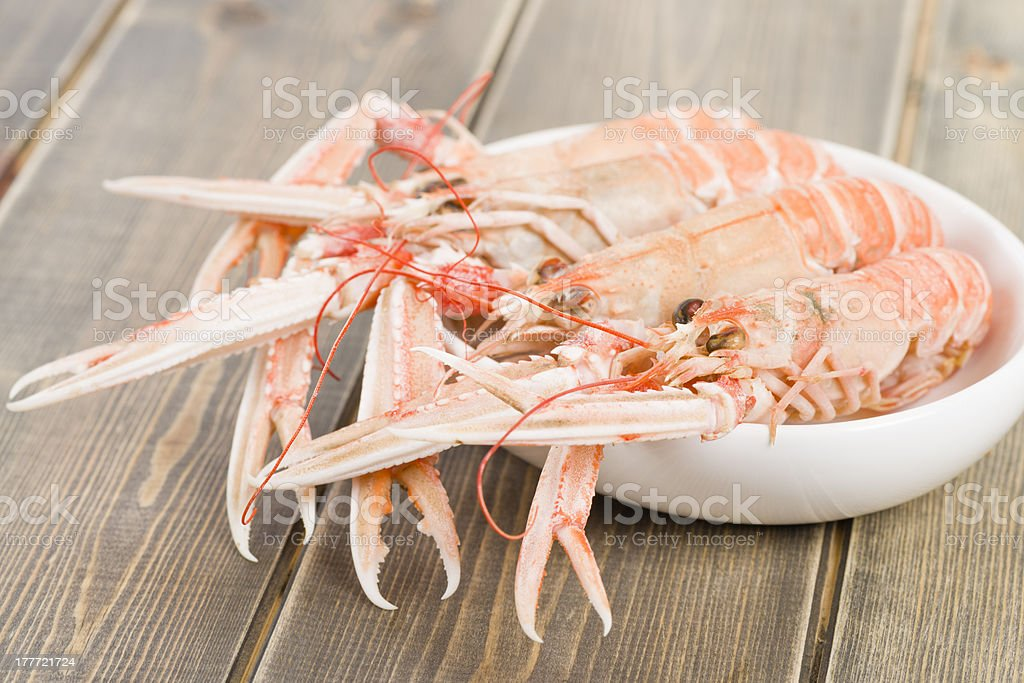 Langoustines in a white bowl on a wooden table stock photo