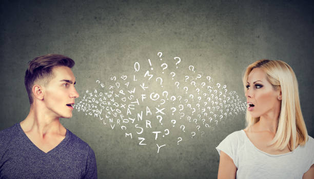 Language barrier concept. Handsome man talking to an attractive young woman with many questions stock photo