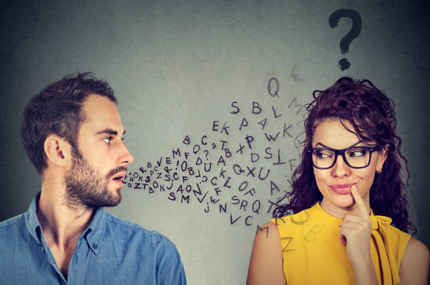Language barrier concept. Man talking to a young woman with question mark stock photo