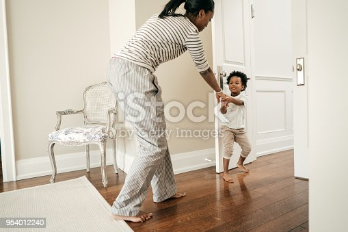 A child is pulling hermom out of the room.