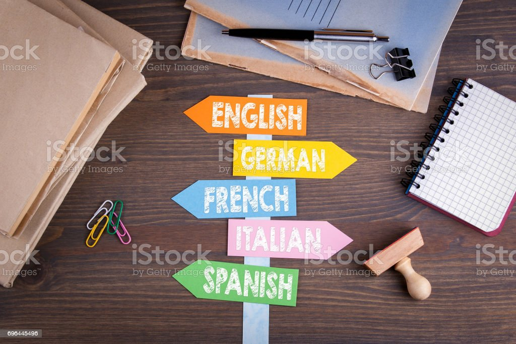 languages concept, English, Italian, German, French, Spanish. Paper signpost on a wooden desk stock photo