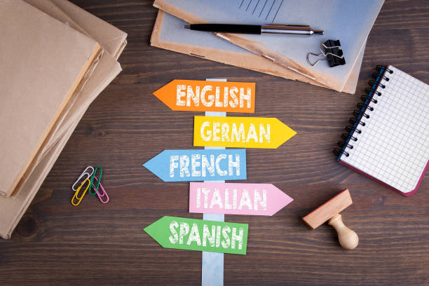 konzept der sprachen, englisch, italienisch, deutsch, französisch, spanisch. papier-wegweiser auf einem schreibtisch aus holz - englandreise stock-fotos und bilder