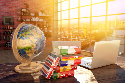 Books with covers in colors of flags of Europe countries, laptop and globe on a table in a modern interior\nSource page for the map texture: http://visibleearth.nasa.gov/view.php?id=57730