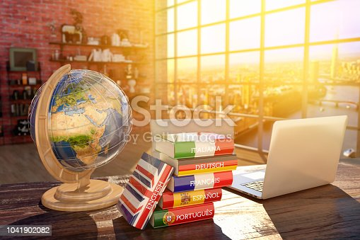 Books with covers in colors of flags of Europe countries, laptop and globe on a table in a modern interior Source page for the map texture: http://visibleearth.nasa.gov/view.php?id=57730