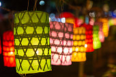 Beautiful Lanna handcraft fabric lamp hanging on rope in front of the Buddhist church at at night.