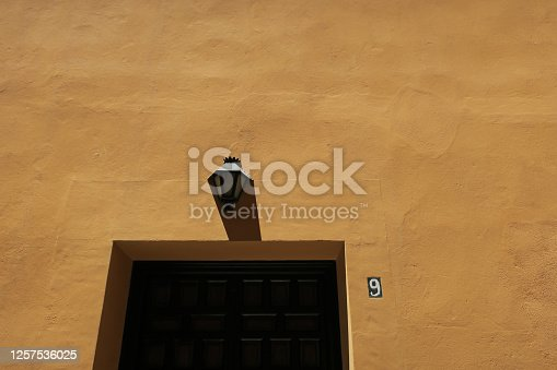 a lantern above a frontdoor on an ochre painted wall of house with number 9