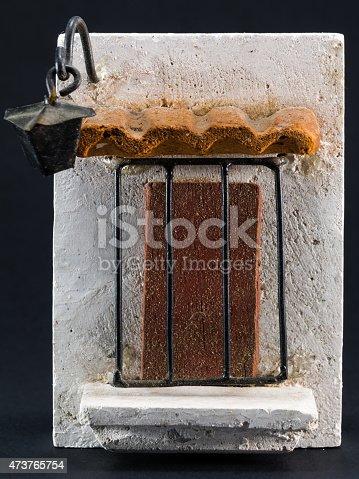 istock Lantern above door, pumice-stone souvenir on black background 473765754