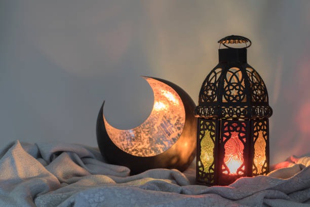lantern and a copper crescent shape on a satin cloth - eid stock pictures, royalty-free photos & images