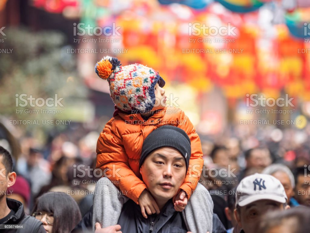 Lantern Festival in the Chinese New Year( Dog year), father hold his son on his shoulder in crowded peoplewith colorful lantern background in Yuyuan Garden. stock photo