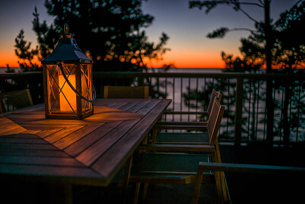 Lantern on a Table by the Ocean at Sunset stock photo