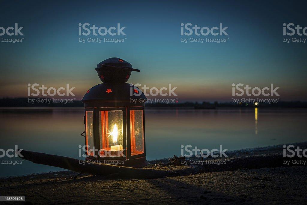 Lantern on sandy beach at the lake stock photo
