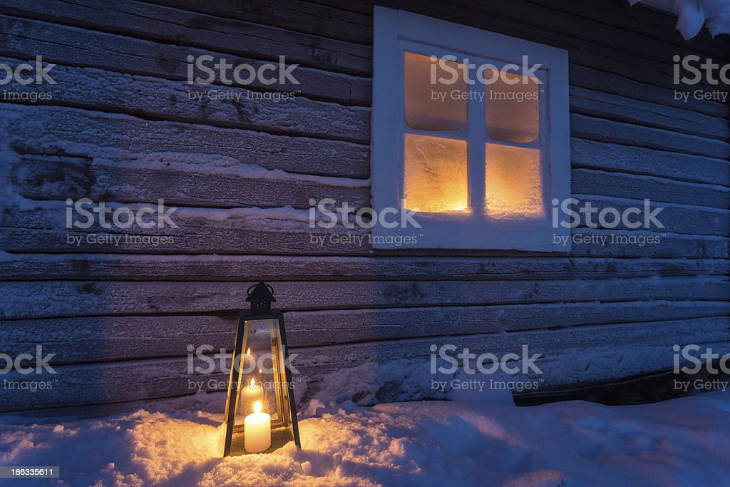 Lantern outside a cottage with frosty window royalty-free stock photo