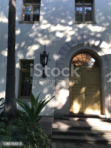 Decorative lantern and sun-dappled doorway in downtown Honolulu