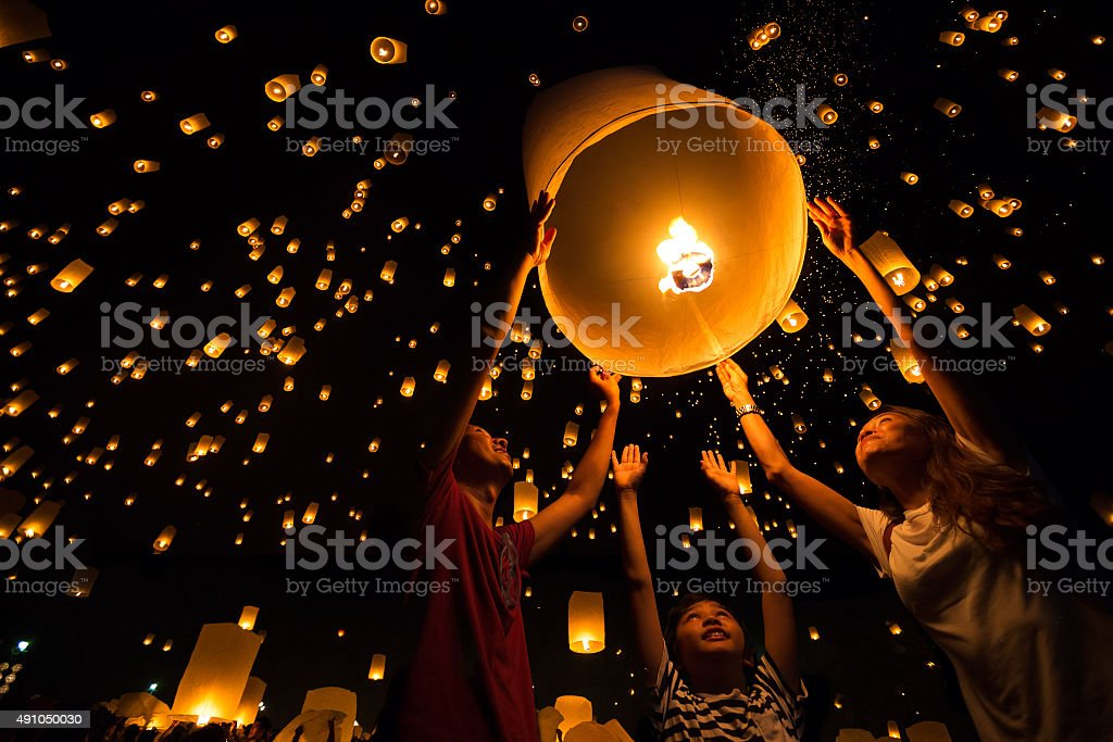 Lantern Thai's Family release sky lanterns to worship buddha's relics in yi peng festival, Chiangmai thailand 2015 Stock Photo