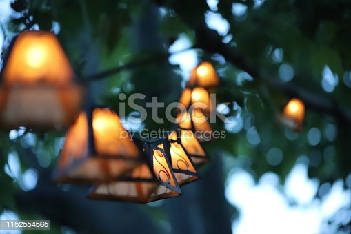 A string of hanging lanterns, with a couple in the middle in focus