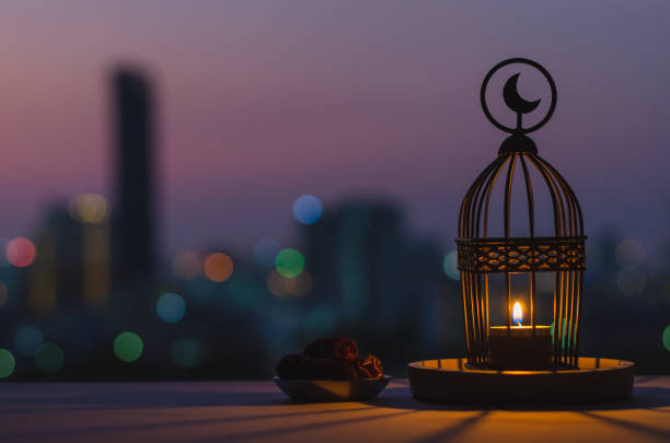 Lantern that have moon symbol on top and small plate of dates fruit with dusk sky and city bokeh light background. Lantern that have moon symbol on top and small plate of dates fruit with dusk sky and city bokeh light background for the Muslim feast of the holy month of Ramadan Kareem. ramadan stock pictures, royalty-free photos & images