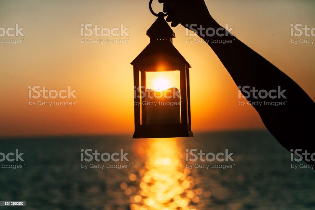 Una linterna con una vela en la mano al amanecer - foto de stock