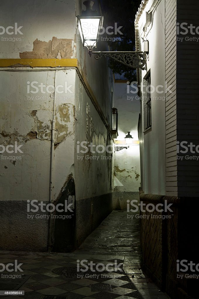 Lanterns light an alley in Seville. stock photo