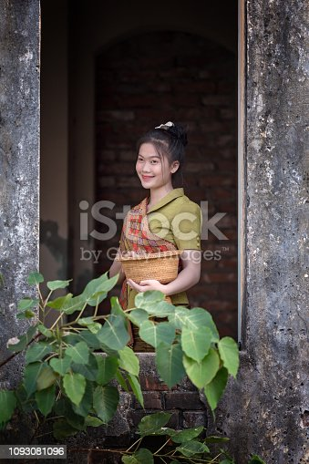 Laos woman she is wearing Lao traditional dress standing in house and cheerful