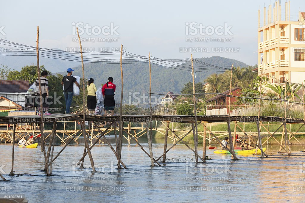 Laotian family crossing bridge in Vang Vieng stock photo