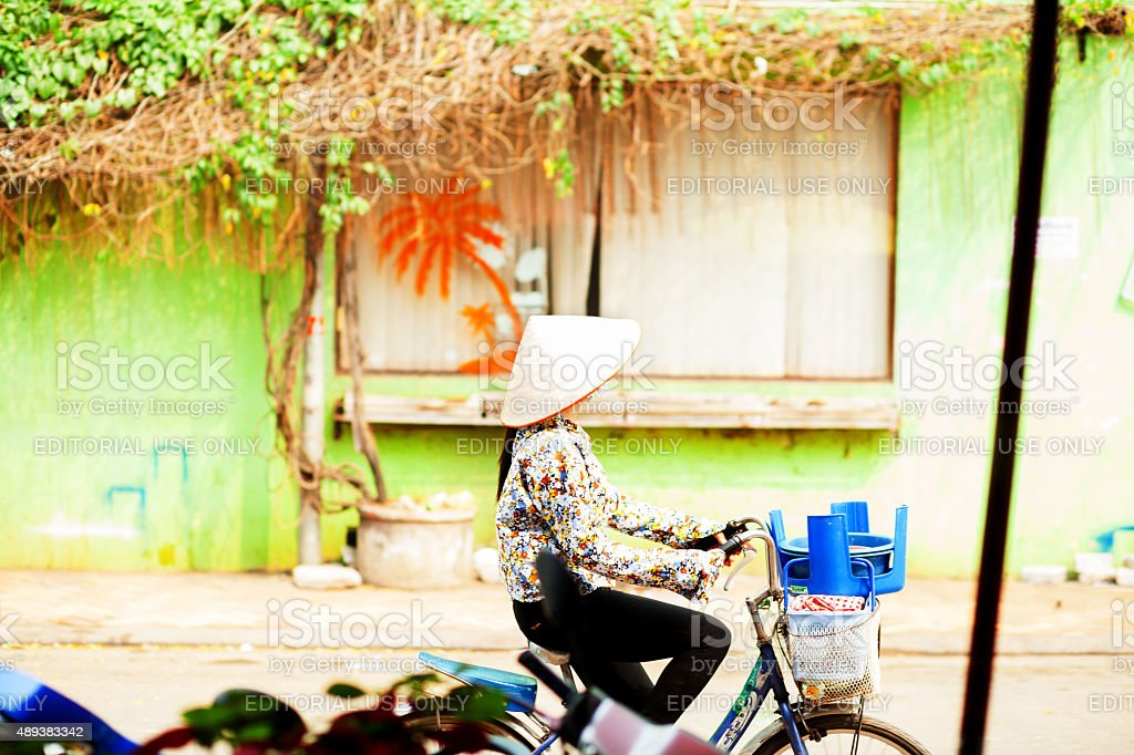 Laotian girl with straw hat on bicycle stock photo
