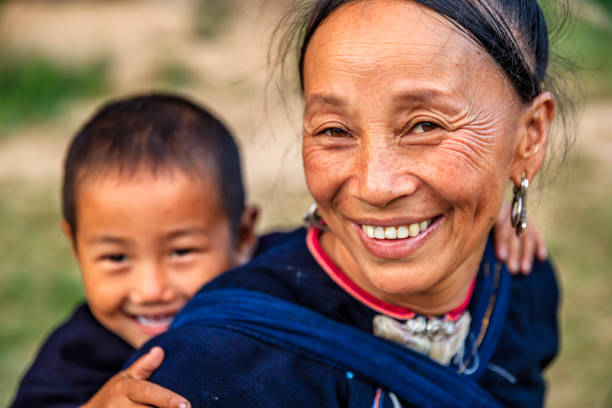 Laotian mother carrying her little son, village in Northern Laos stock photo