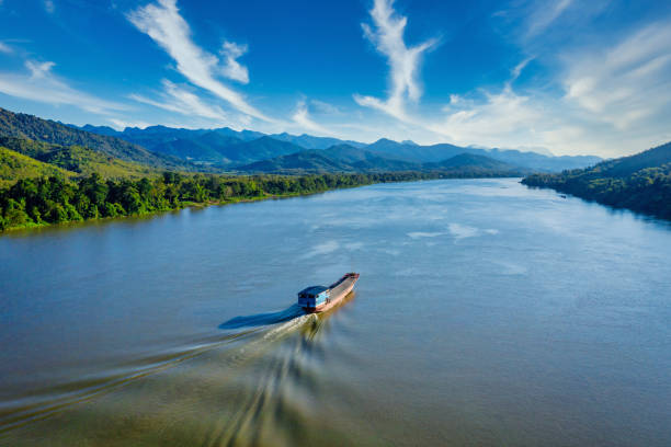 laotian ship cruising along the mekong river in laos aerial drone view - mekong river stock pictures, royalty-free photos & images