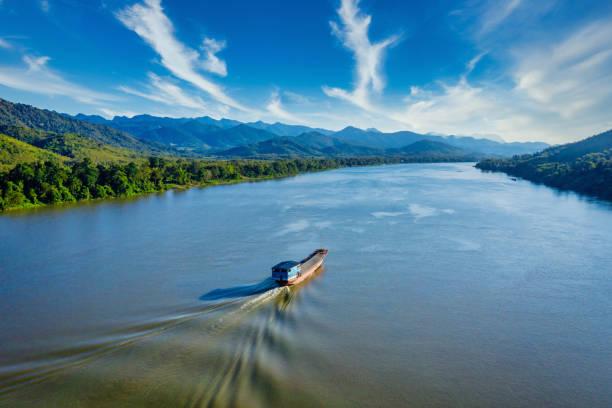 Laotian ship cruising along the Mekong River in Laos Aerial Drone View