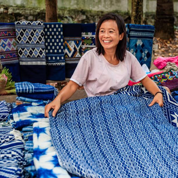 laotische frau verkaufen traditionelle textilien auf ein morgenmarkt, luang prabang, laos - laos stock-fotos und bilder