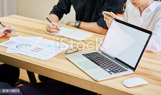 istock Laptop a blank screen, on the desk,  woman holding a blank screen smartphone, colleagues are using smartphone and documents. Teamwork ideas work faster. 878119374